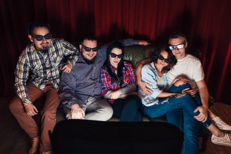 年轻愉快的人民公司在家看电视 库存图片