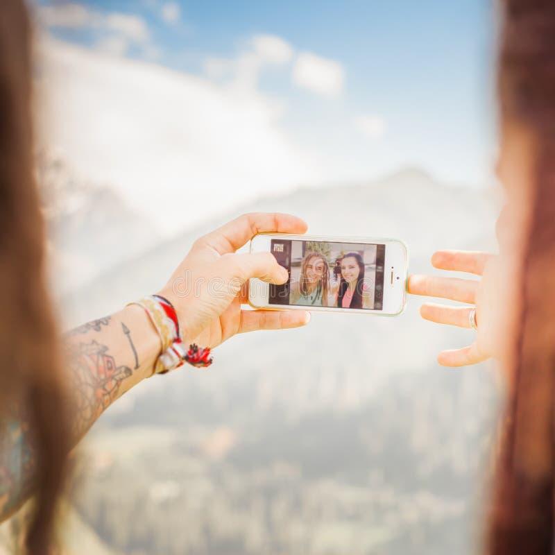 愉快的人民在手机使selfie在山室外 库存图片