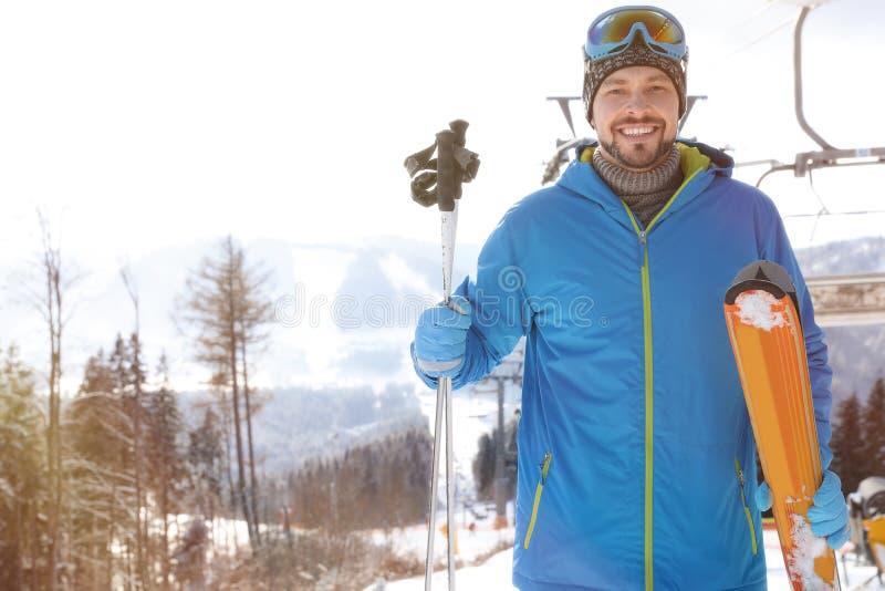 愉快的人用在驾空滑车附近的滑雪设备在山区度假村 背景海滩异乎寻常的做的海洋沙子雪人热带假期白色冬天 免版税图库摄影