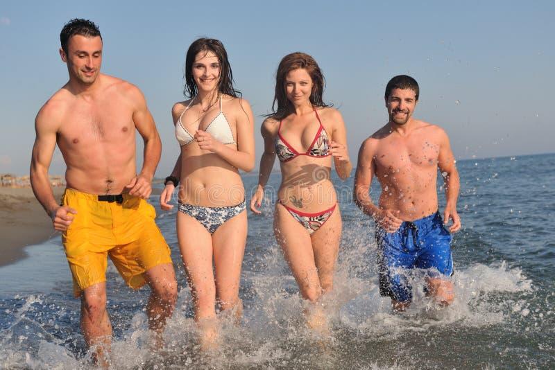 愉快的人组有在海滩的乐趣和运行中 免版税库存图片