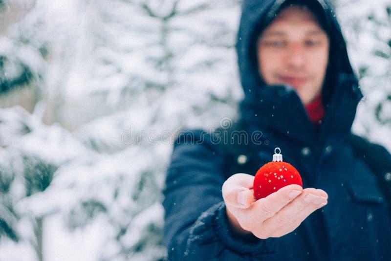 愉快的人藏品红色圣诞节球在他的在积雪的冷杉圣诞树前面的手上,户外 选择聚焦 免版税库存照片