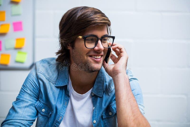 愉快的人谈话在电话在办公室 库存图片