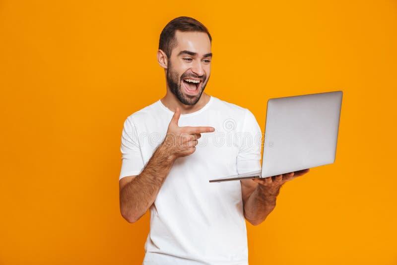 愉快的人30s画象白色T恤的使用银色膝上型计算机,被隔绝在黄色背景 免版税库存图片