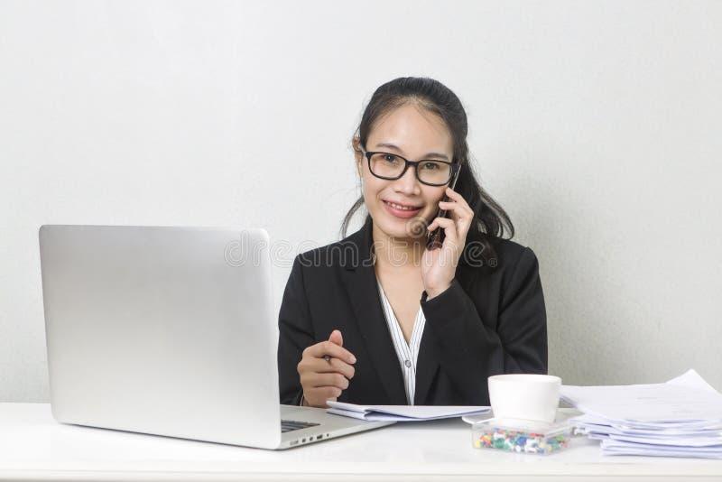 愉快的企业亚裔妇女与膝上型计算机一起使用在白色工作表上 库存照片