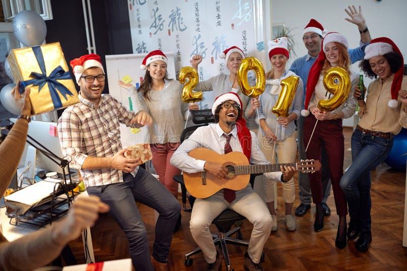 愉快的企业工作者有乐趣和跳舞在圣诞老人帽子在Xmas党和交换礼物 免版税库存图片
