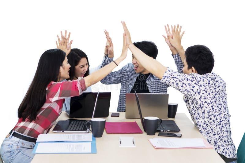 愉快的企业队一起给高五只手 免版税库存图片