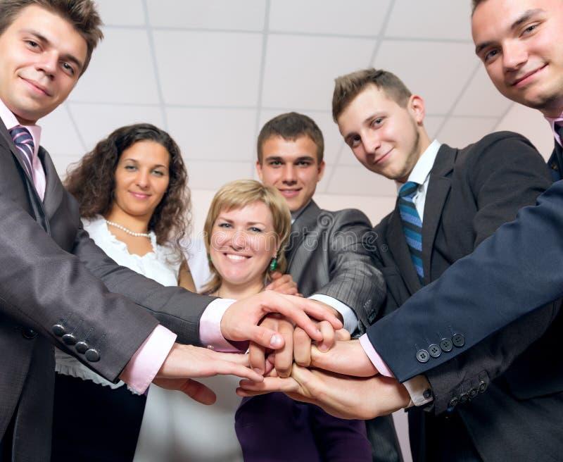 愉快的企业队团结的手和微笑 免版税库存图片