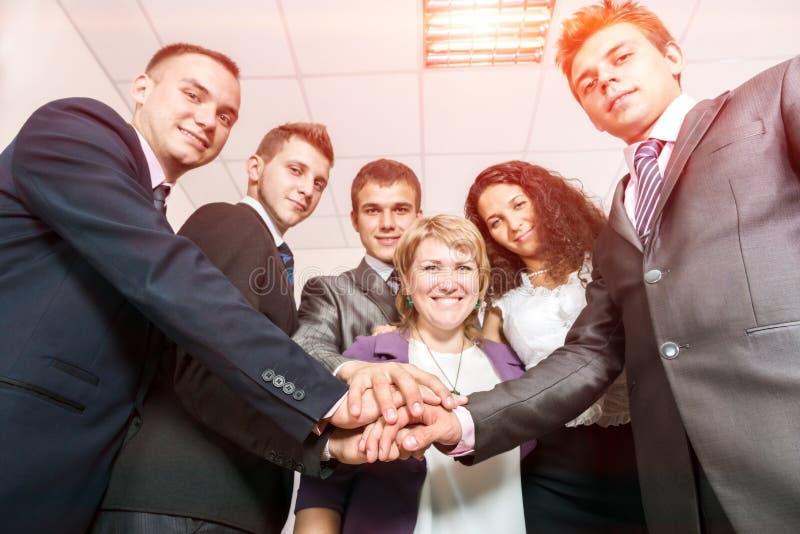 愉快的企业队团结的手和微笑 免版税库存照片