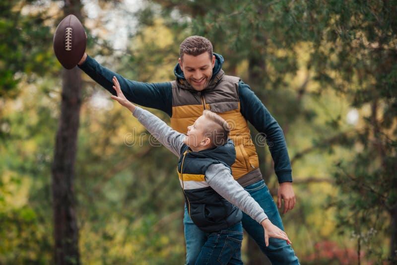 愉快的使用与橄榄球球的父亲和儿子 库存图片