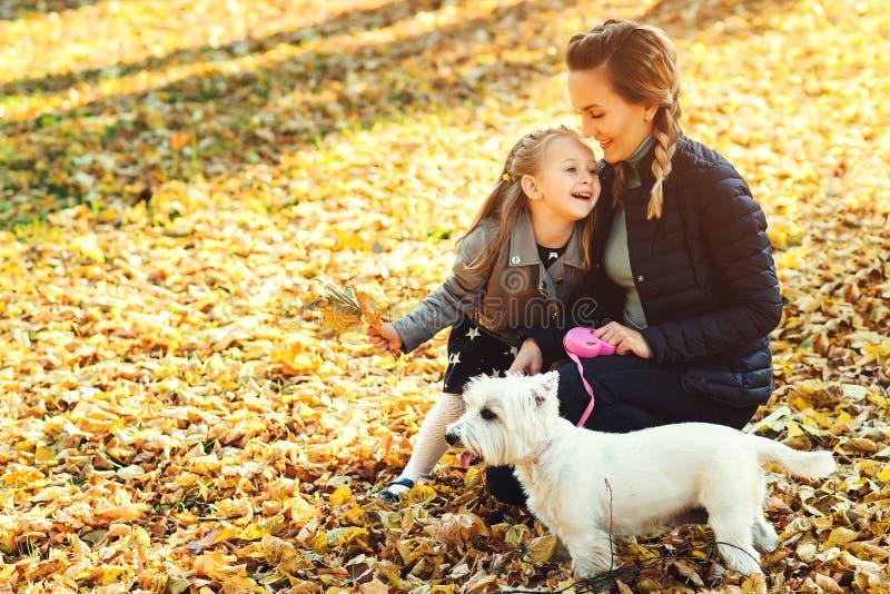 愉快的使用与狗的母亲和她的女儿在秋天公园 家庭、宠物、家畜和生活方式概念 秋天时间 Ha 免版税库存图片