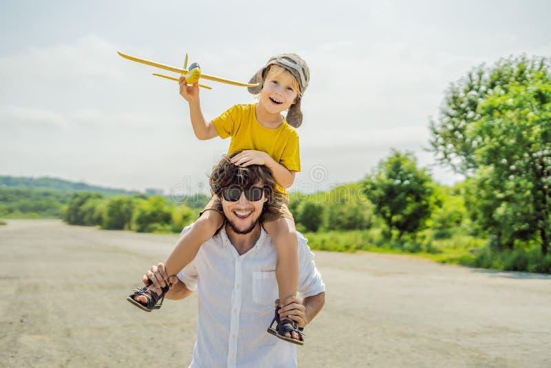 愉快的使用与玩具飞机的父亲和儿子反对老跑道背景 旅行与孩子概念 免版税图库摄影