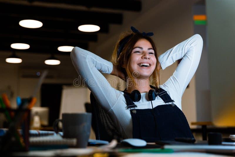 愉快的使用个人计算机计算机工作的年轻女人图表设计师与片剂在晚上在办公室 免版税库存照片