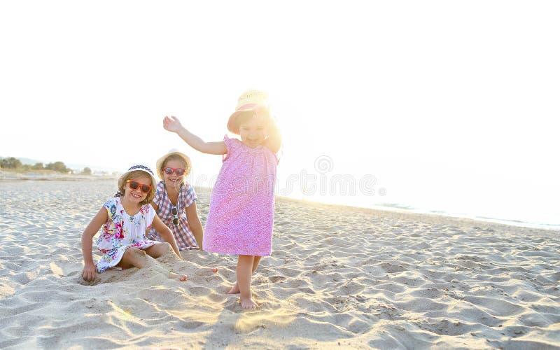 愉快的使用在一个美丽的海滩的沙子的女婴和她的姐妹 免版税库存图片