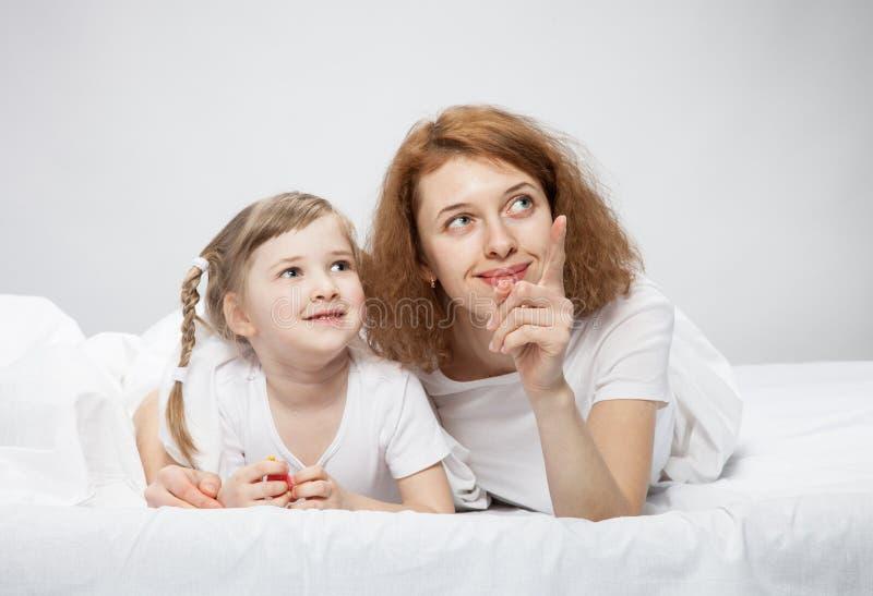 愉快的使用在床上的母亲和她的小女儿 免版税库存照片