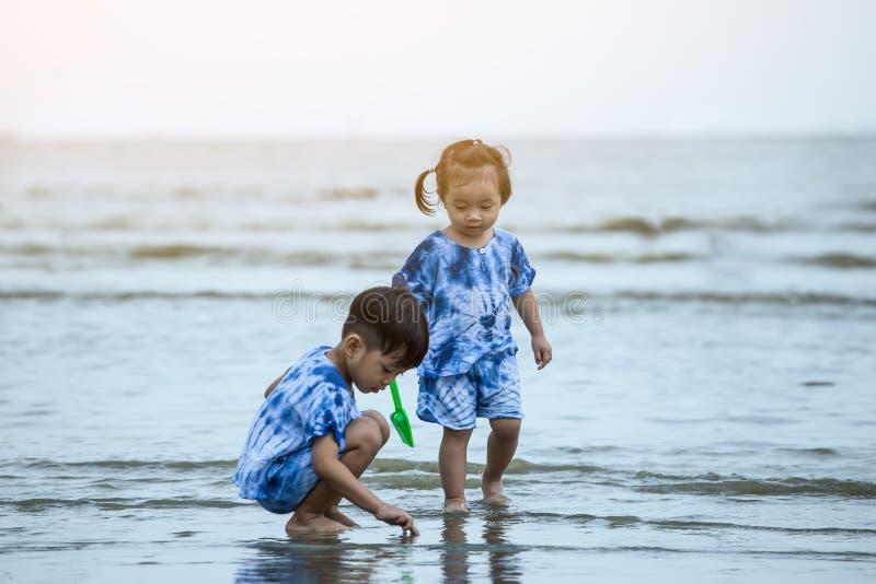 愉快的使用在海滩的男孩和女孩 库存照片