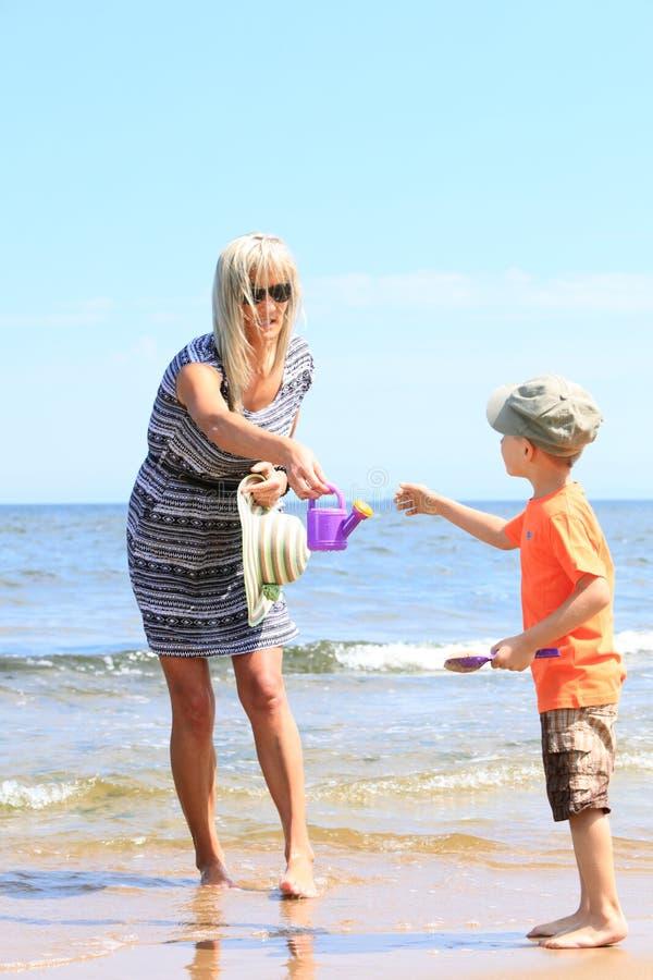 愉快的使用在海滩的母亲和儿子 库存图片