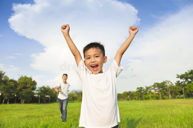 愉快的使用在草甸的父亲和儿子 免版税库存图片