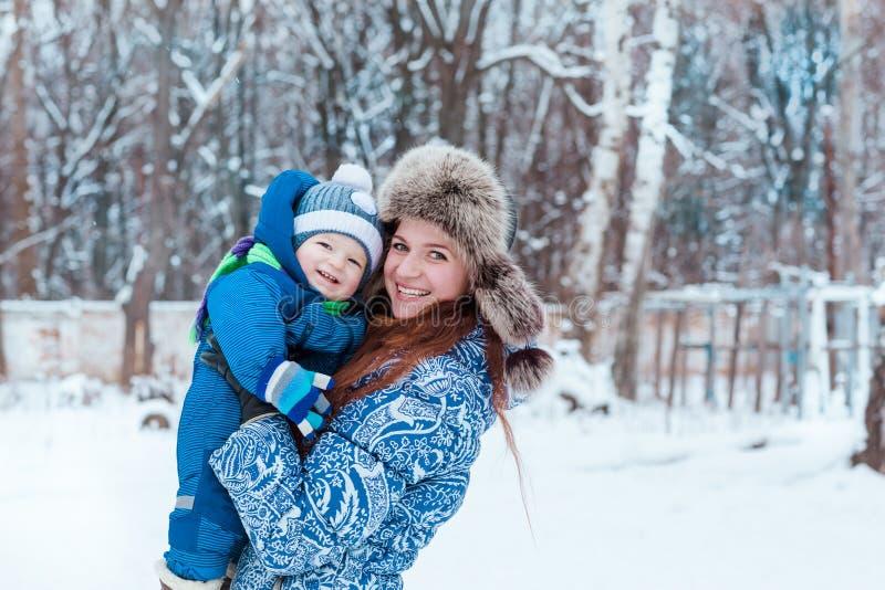 愉快的使用在雪的母亲和婴孩 免版税库存照片