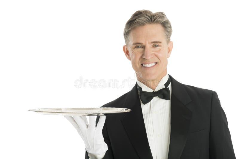 愉快的侍者画象无尾礼服的有服务盘子的 免版税库存照片