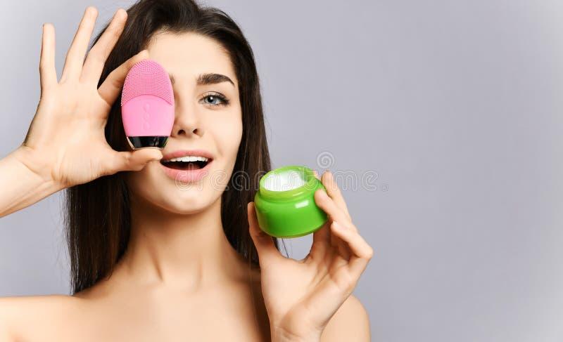 愉快的俏丽的妇女用桃红色皮肤的面孔刷子硅树脂洗涤的设备盖她的眼睛并且显示一个瓶子面霜 库存图片