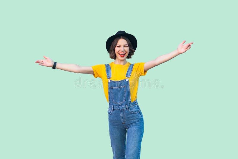 愉快的俏丽的少女画象蓝色牛仔布总体、黄色衬衣,黑帽会议身分与被举的胳膊和看的 图库摄影