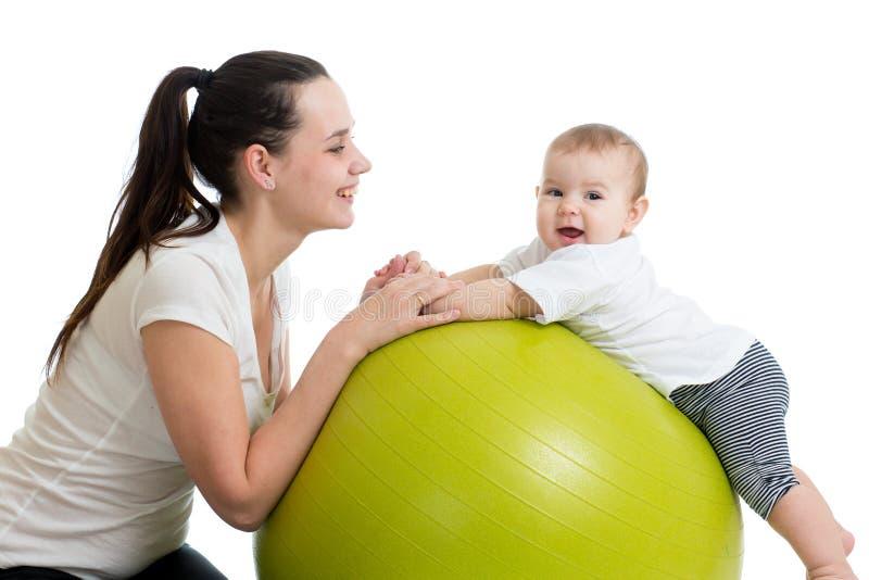 愉快的做健康体操的母亲和婴孩在适合球 免版税库存图片