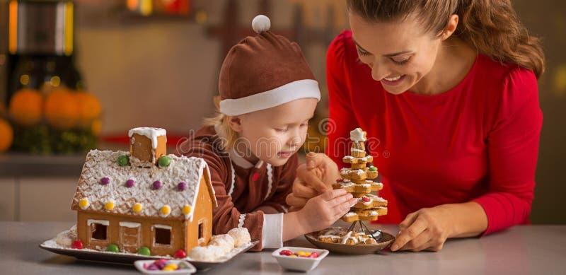 愉快的做圣诞节曲奇饼房子的母亲和婴孩 库存照片