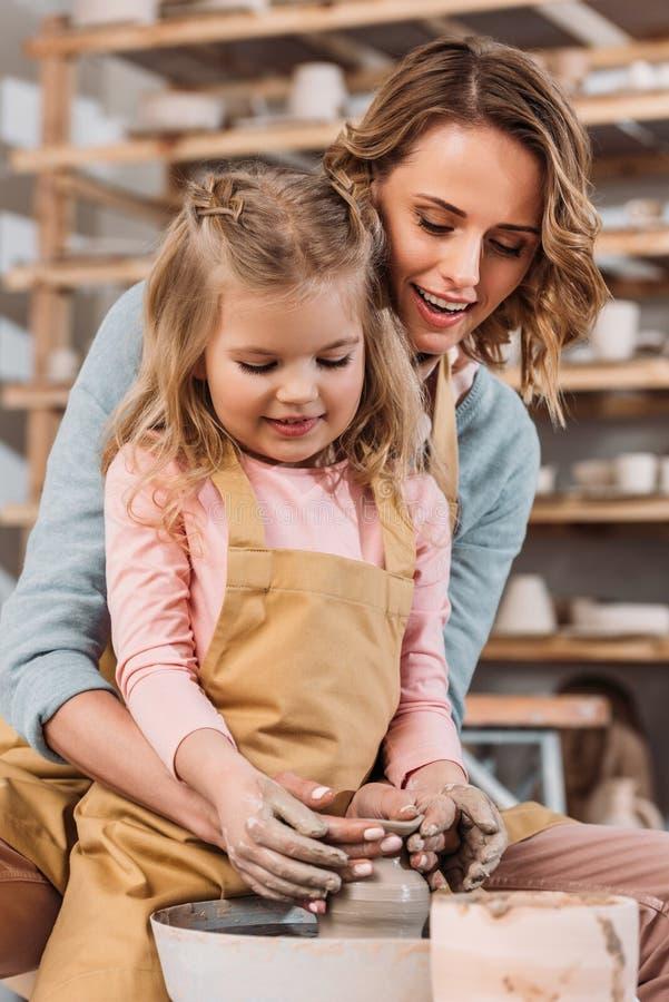 愉快的做陶瓷罐的母亲和女儿 免版税库存图片