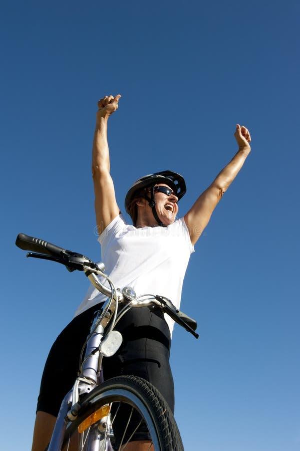 愉快的健康女性骑自行车者 库存照片