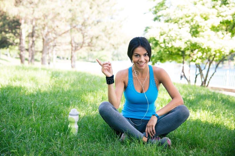 愉快的健身妇女坐绿草 免版税库存图片