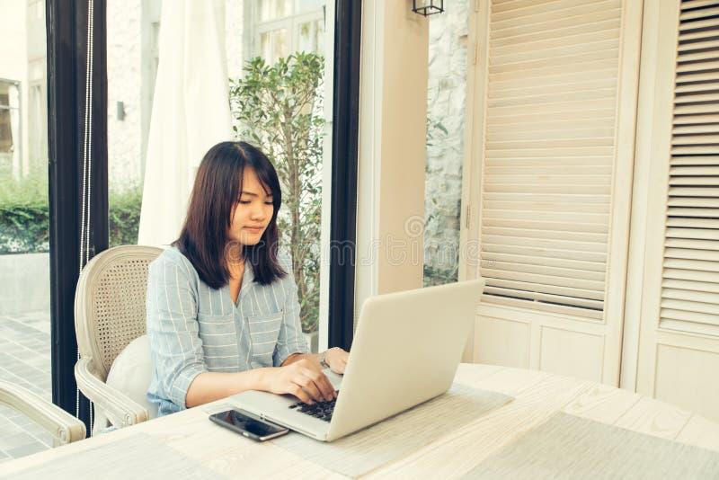 愉快的偶然美丽的妇女观看的录影或享受在坐在咖啡店大阳台的膝上型计算机的娱乐内容 库存图片