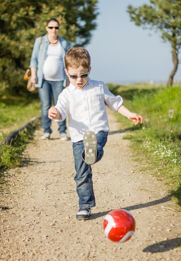 愉快的儿子使用与足球的和他的pregnacy母亲神色 免版税库存照片