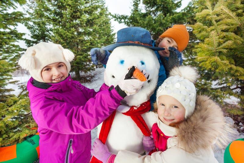愉快的儿童修造快乐的雪人特写镜头  库存图片