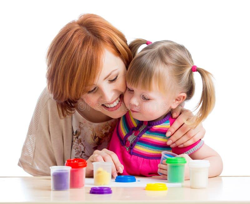 愉快的儿童女孩和母亲使用与五颜六色的黏土玩具 免版税库存图片