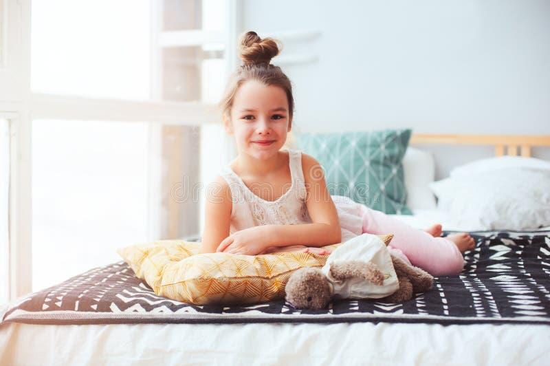 愉快的儿童女孩在清早醒在她的屋子里 免版税库存图片