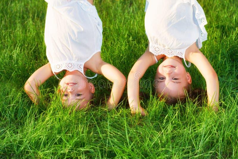 愉快的儿童孪生姐妹颠倒在夏天 库存图片