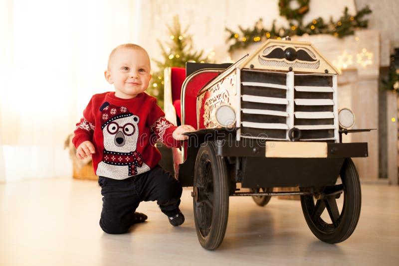 愉快的儿童男孩使用与在圣诞树的背景的儿童的玩具汽车 库存照片