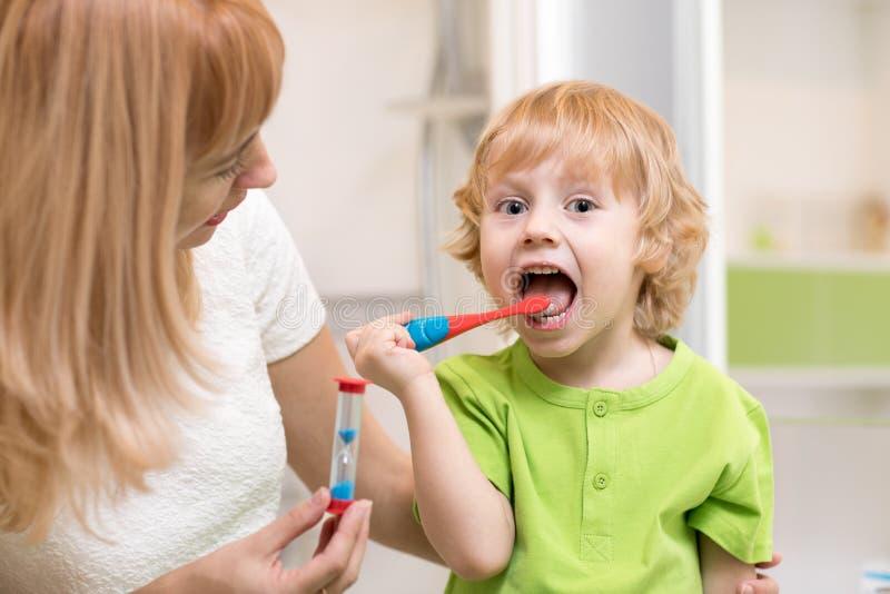 愉快的儿童男孩掠过的牙在卫生间里临近镜子 他的清洗作用的母亲监视准确性和时期与 库存图片