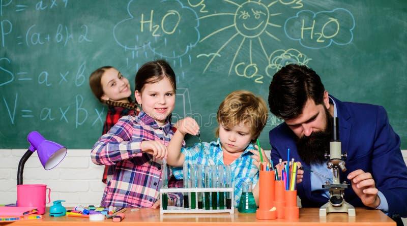 愉快的儿童老师 试验化学制品或显微镜在实验室 r o ?? 库存图片