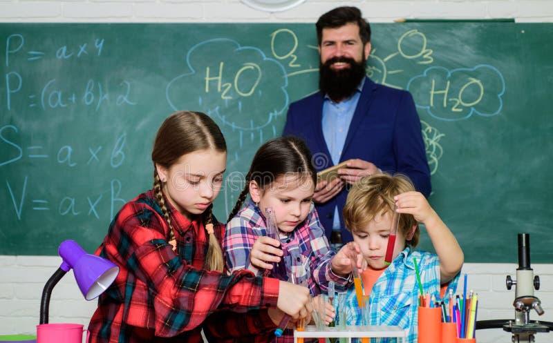 愉快的儿童老师 r 在实验室外套的孩子学会化学的在学校实验室 做实验与 免版税图库摄影