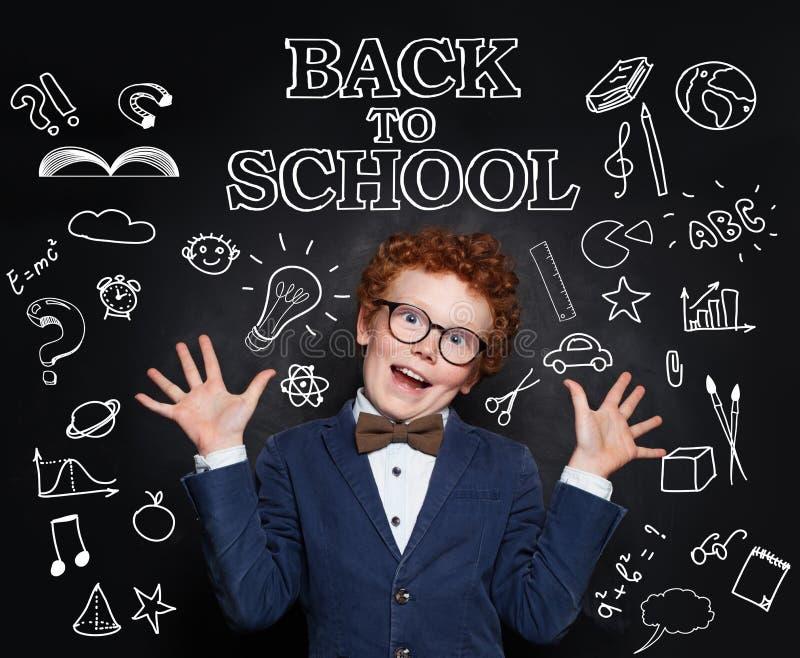愉快的儿童聪明的学生男孩在黑板背景的教室 r 库存照片