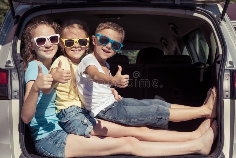 愉快的兄弟和他的两个姐妹在汽车坐在 图库摄影