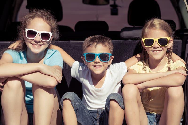 愉快的兄弟和他的两个姐妹在汽车坐在 免版税库存图片