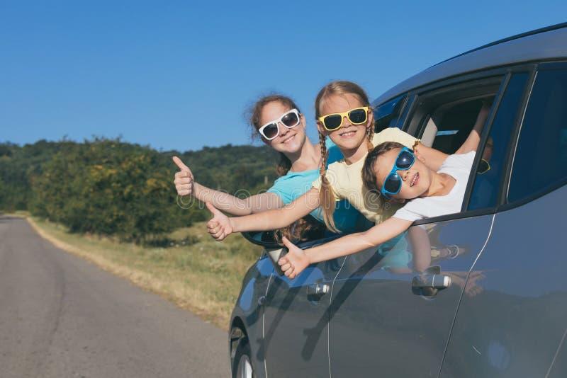 愉快的兄弟和他的两个姐妹在汽车坐在 库存照片