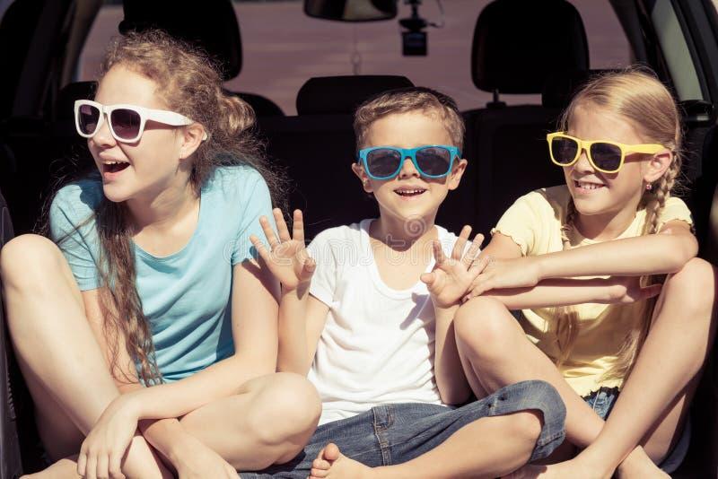 愉快的兄弟和他的两个姐妹在汽车坐在 库存图片