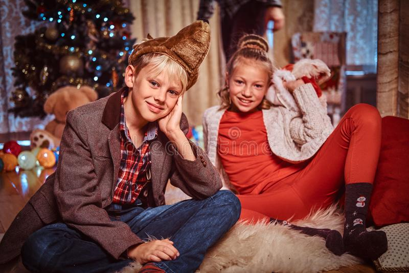 愉快的兄弟和姐妹在家坐毛皮地毯在圣诞树附近 免版税库存照片