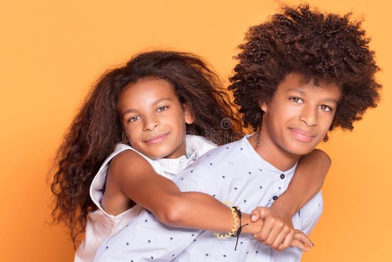 愉快的兄弟和姐妹有非洲的发型的 免版税库存照片