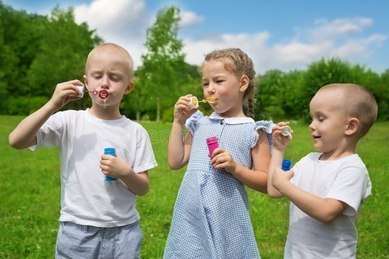 愉快的兄弟和姐妹膨胀肥皂泡 免版税库存图片