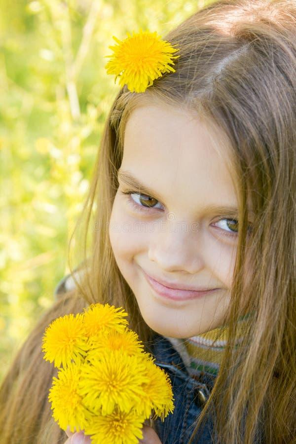 愉快的八岁的女孩画象用蒲公英在手上,反对绿色叶子背景  库存照片