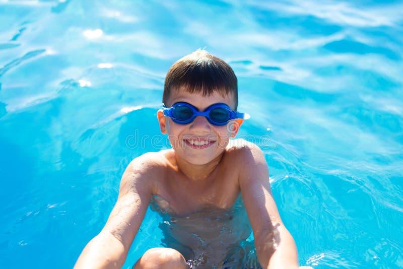 愉快的兴高采烈的小男孩为在游泳的仰泳开始做准备 库存图片